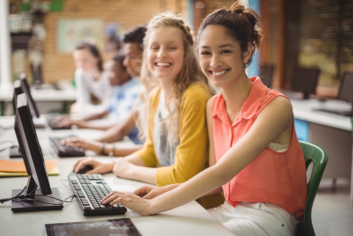 16 Year Old Girls Sitting At A Computer Desk Smiling for the Camera