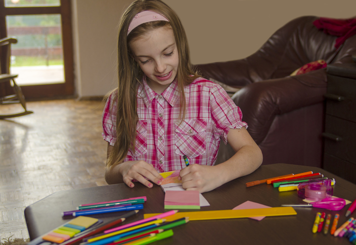 Image of a 10 Year Old Girl Doing Some Drawing at a Table
