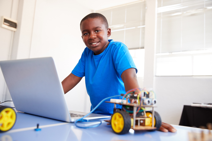 Image of an 11 Year Old Boy with a Robot toy and computer