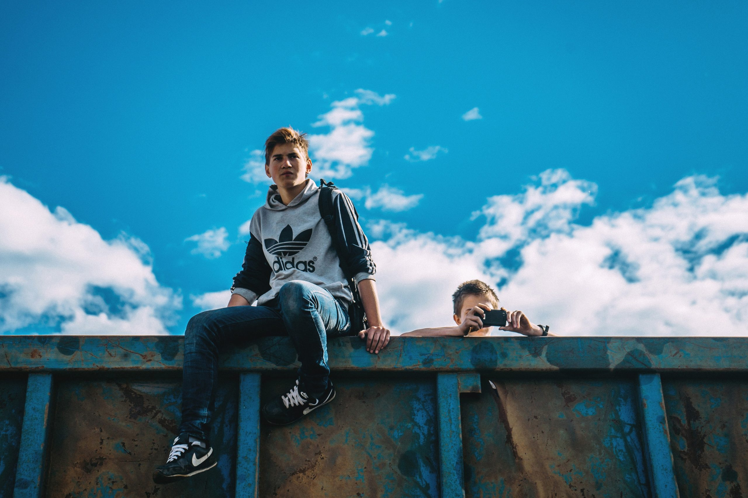 image of two 18 year old guys outside climbing over a dumpster