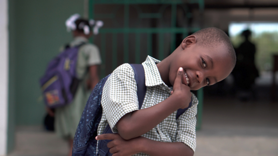 Image of a 6 Year Old African American Boy Smiling with his backpack on at school