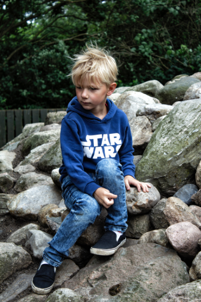 Image of a 7 Year Old Boy Sitting on some rocks at a Park