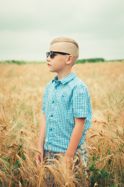 Image of an 8 Year Old Boy Wearing Sunglasses while standing in a wheat field